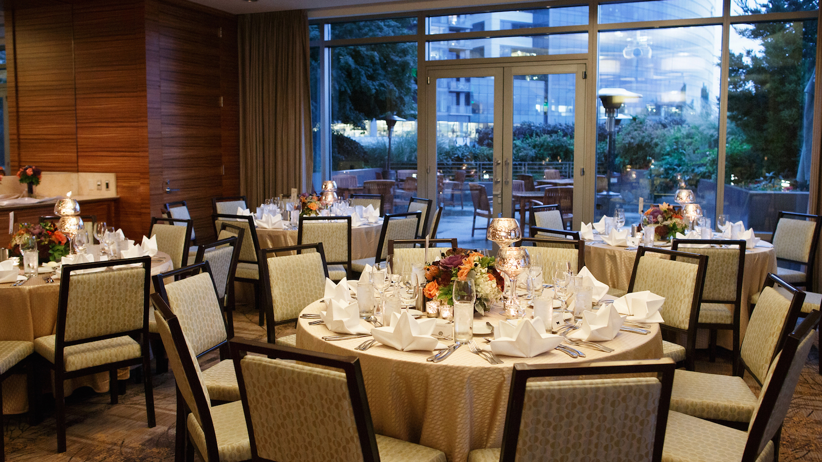 Lakefront room at Pan Pacific Seattle for upscale event with round tables with settings and centerpiece flower arrangements