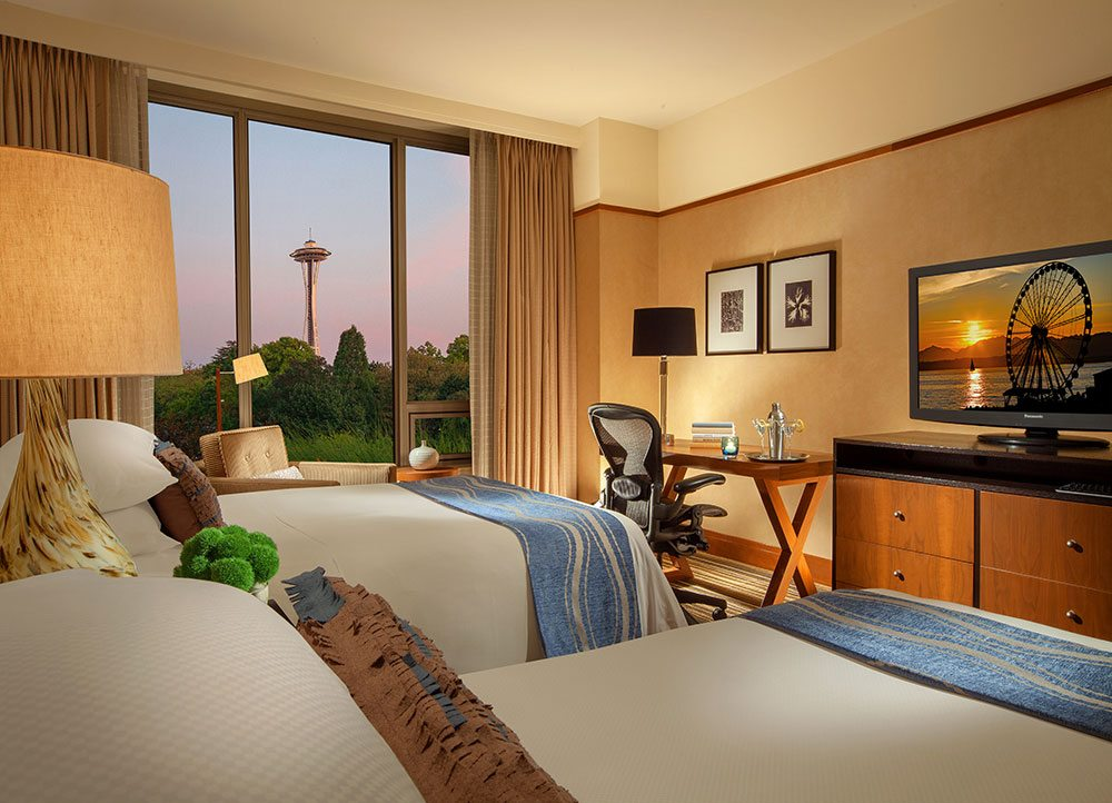 Deluxe Double room with TV, dresser, desk and chair, and view of the Seattle Space Needle