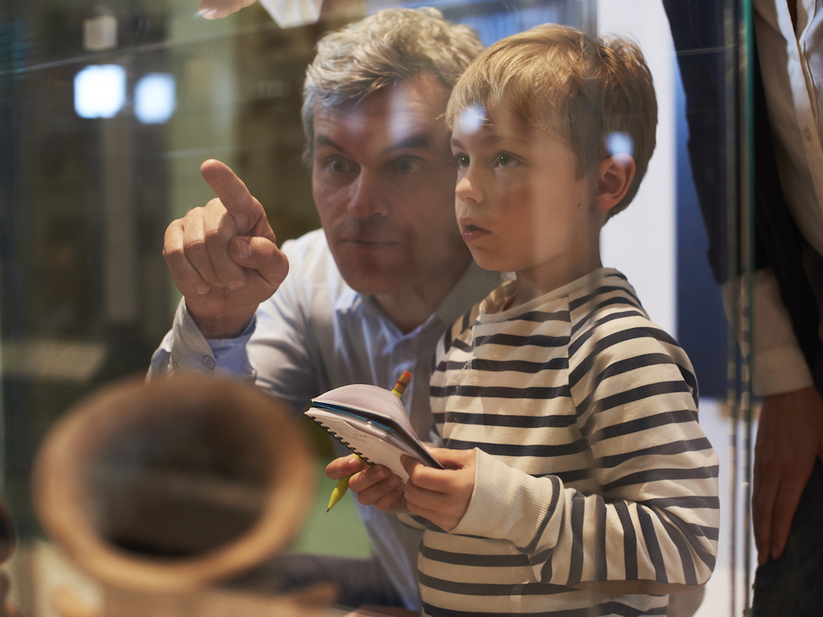 Father And Son Look At Artifacts In Case On Trip To