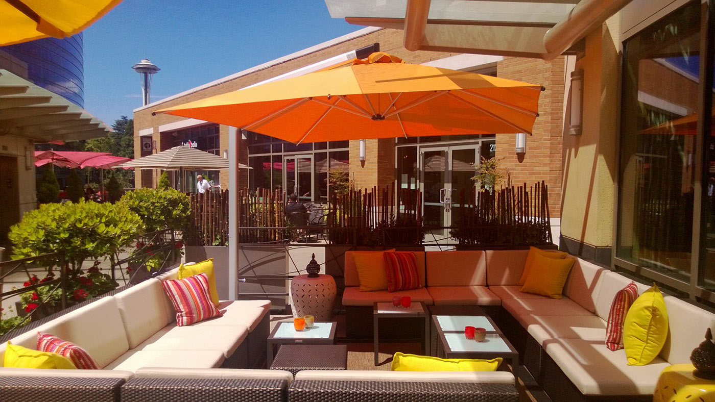 patio area for lobby bar on a sunny day with enclosed cushioned seating, tables and large patio umbrella