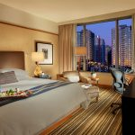 premium room with king bed with tray of sushi on top, and view of city buildings