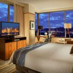 Space Needle corner suite with king bed, chair, ottoman, desk with ergonomic chair, and flat screen TV