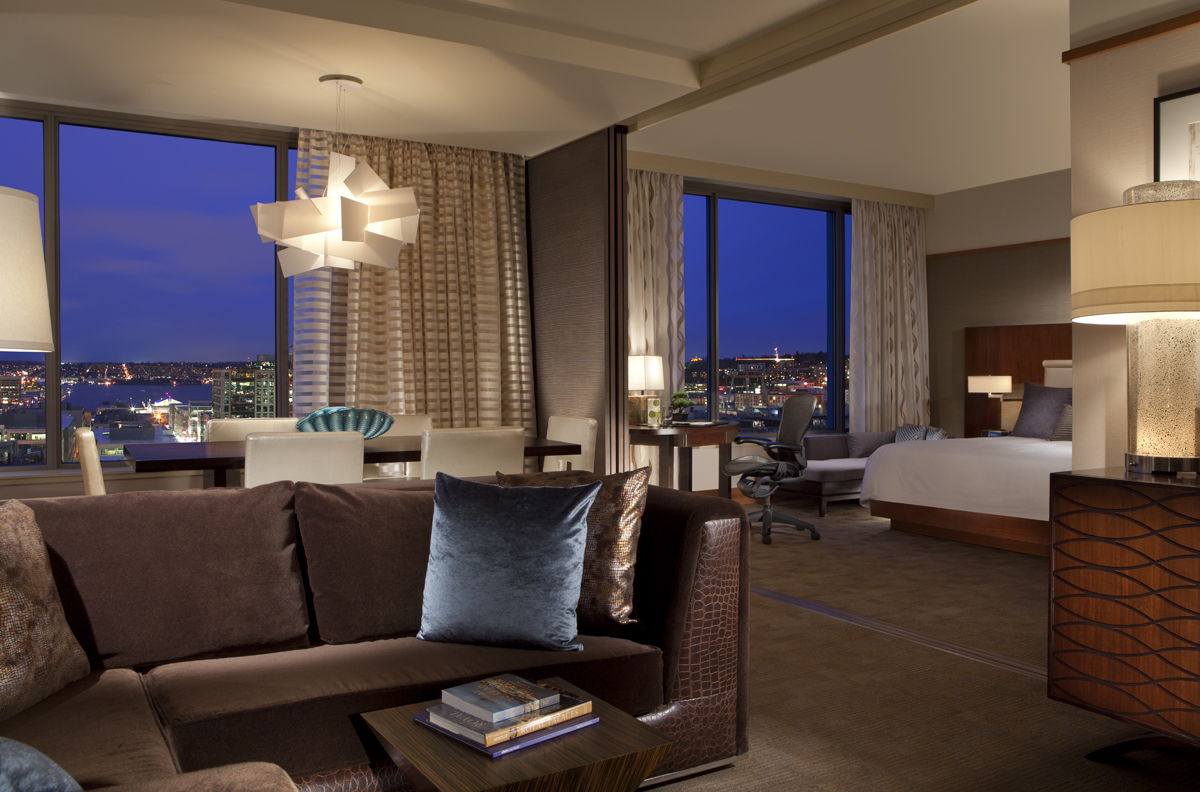 Space Needle Suite with sectional sofa, table with seating for six, desk with chair, and bed