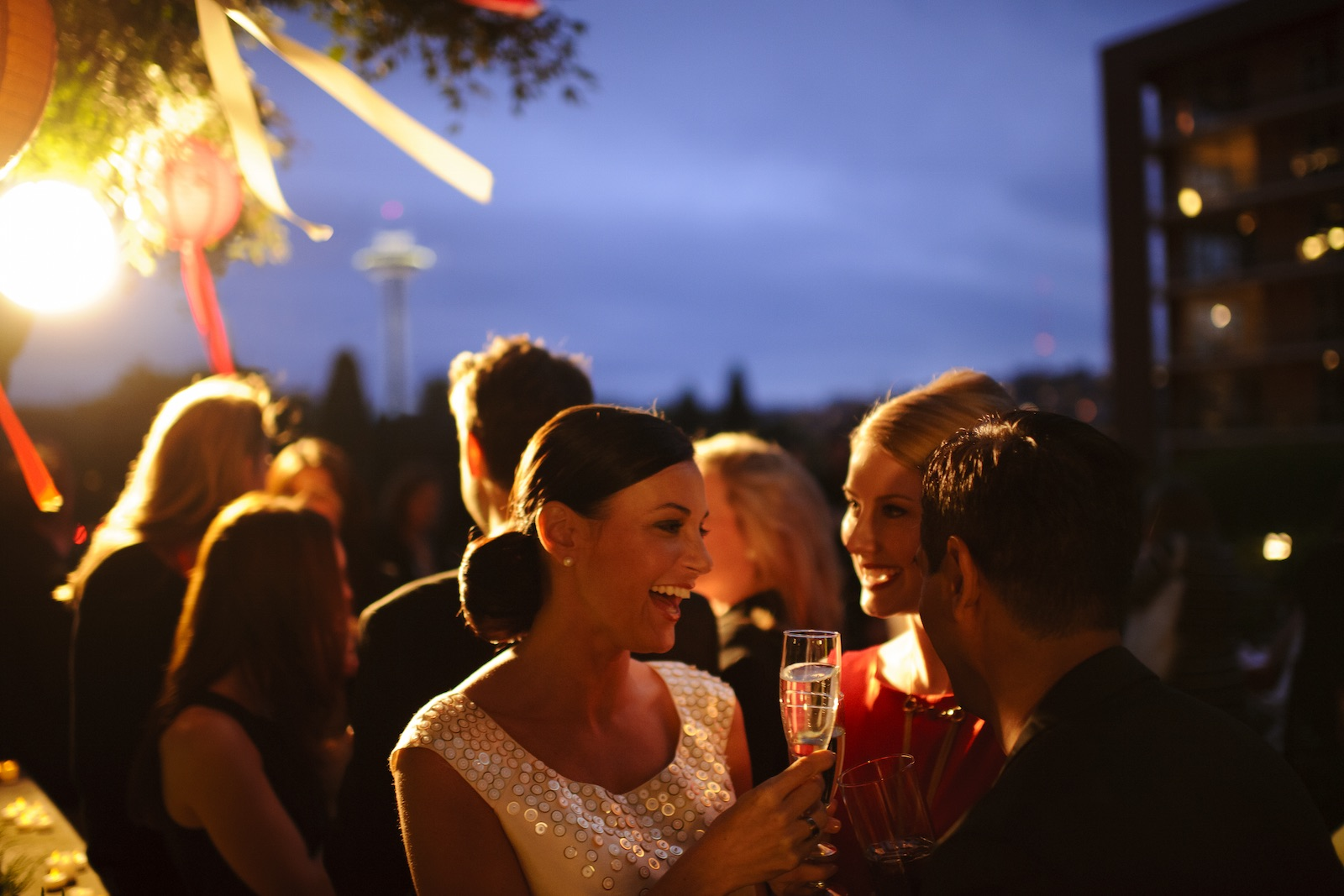 two women hold wine glasses, smiling, as other people mingle in the background at dusk at an outdoor reception, as the Seattle Space Needle is visible in the background