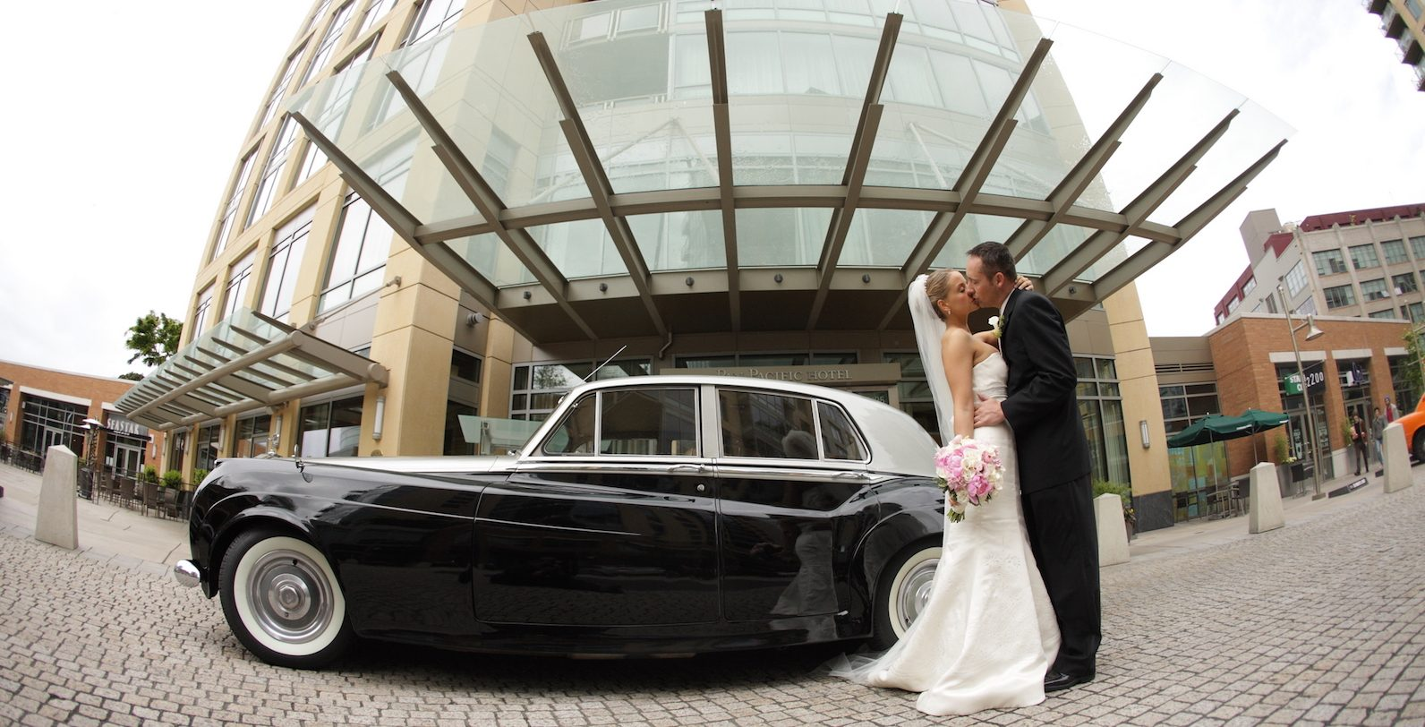 Bride and groom standing, kissing next to antique car parked in front of entrance to Pan Pacific Seattle Hotel
