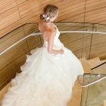 side view of woman wearing wedding dress walking down stairs with wood-paneled walls