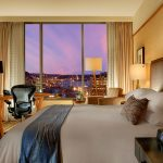 Deluxe Queen City view room with bed, desk, ergonomic office chair, and panoramic view of the city