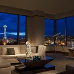 penthouse with sectional sofa, telescope, and panoramic view of the Seattle Space Needle and the city