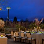 outdoor terrace at night at Pan Pacific Seattle Hotel with view of Seattle Space Needle and large table for up to 16 guests