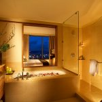 Large bathroom with bathtub filled with water and rose petals
