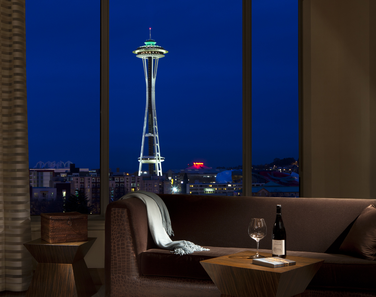 View of Seattle Space Needle illuminated at night from Space Needle Suite in Pan Pacific Seattle Hotel, with loveseat and table with bottle of wine