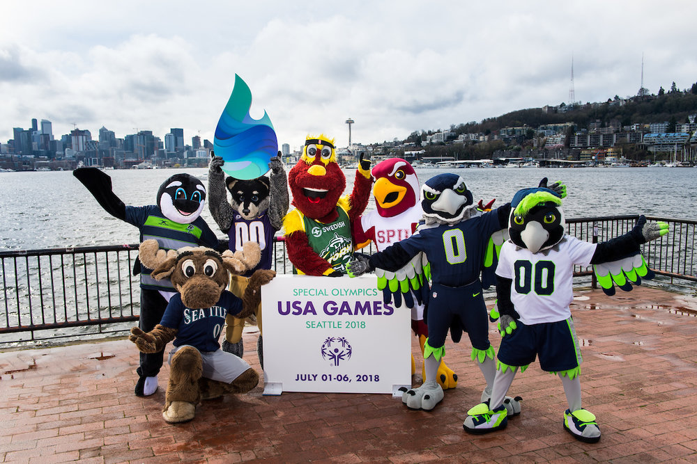 Photo by Rod Mar of sport mascots holding a sign for Special Olympic games of 2018 in Seattle