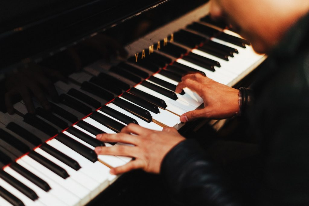 close up of hands playing piano