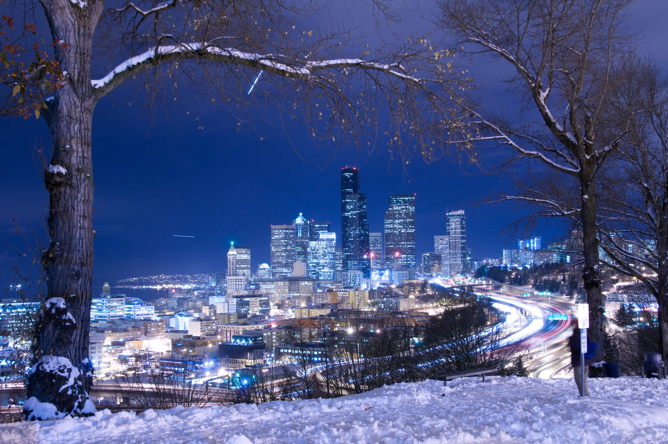 aerial view of seattle washingtone in the winter at night with city lights and snow