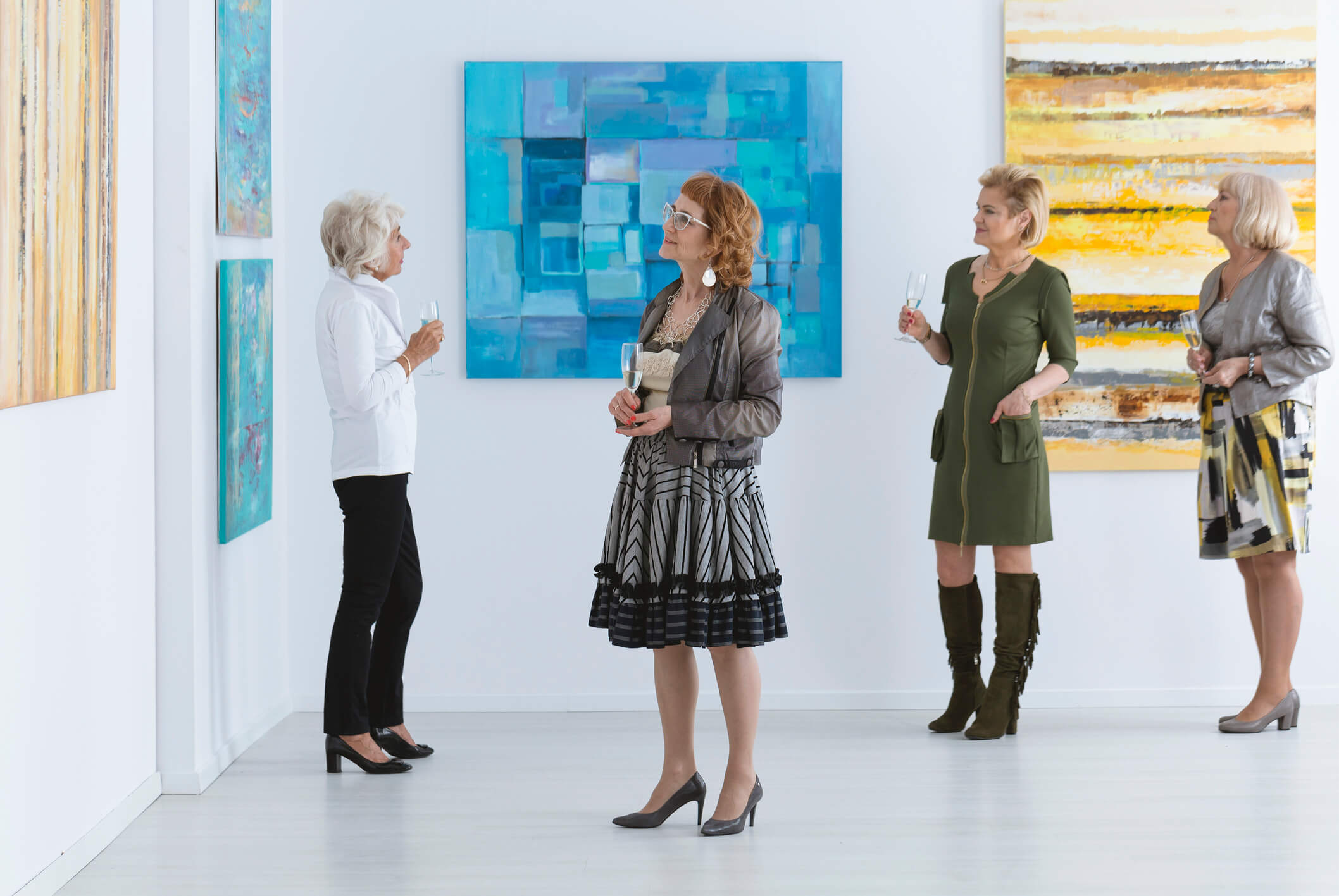 four women looking at art in a museum