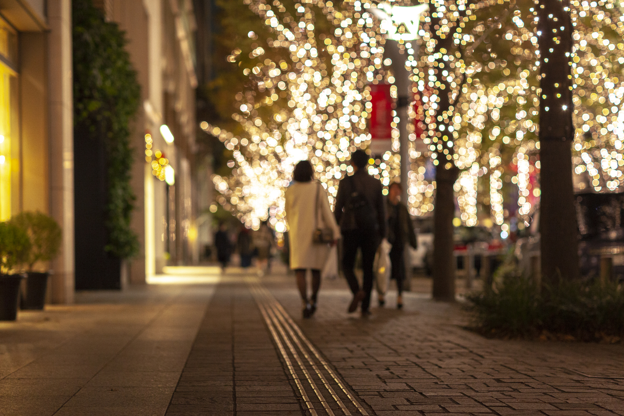 People walking down city street at night lit up by white Christmas lights